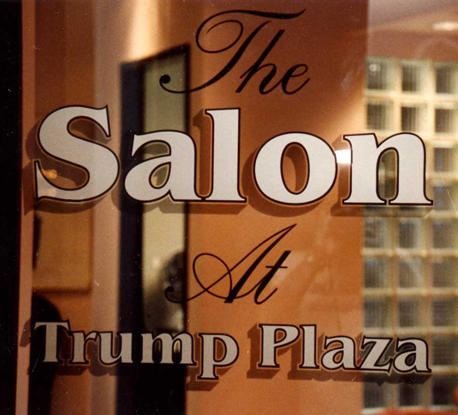 Screen printed glass of a Trump Plaza store reading 'The Salon At Trump Plaza'