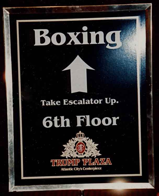 a sign in a stanchion that reads 'Boxing, Take Escalator Up. 6th Floor' with the Trump Plaza logo