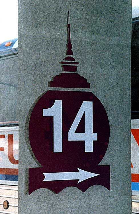 a sign of a silhouette of the top of a building with the number '14' and an arrow on top of it