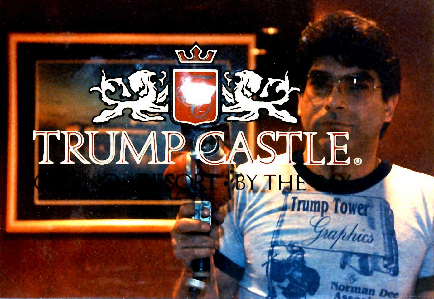owner/founder Norman Dee posing with heat gun and screen printed glass that reads 'Trump Castle'