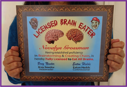 A physical sample of our Licensed Brain Eater license mounted onto posterboard. It reads 'Licensed Brain Eater - Novalyn Grossman - having established proficiency in Brainstorming & Creating Chaos, is hereby Fully Licensed to Eat All Brains. - Bray Needor, Headmaster - Eaton Hedds, Commissioner'.